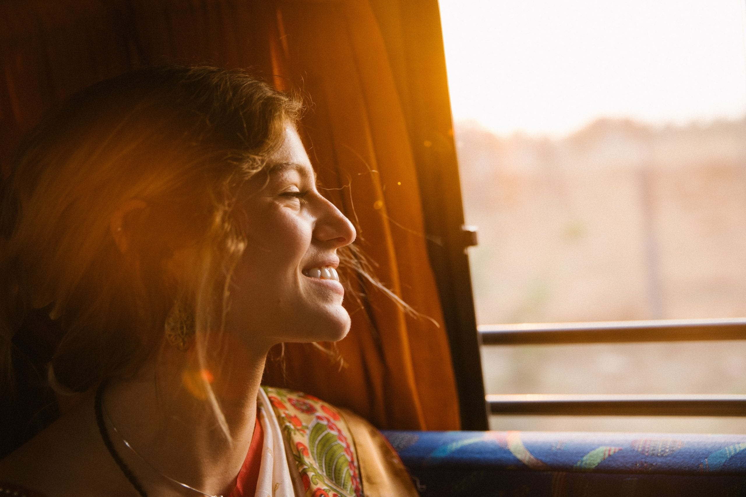 young-woman-looking-out-the-window-smiling-confident